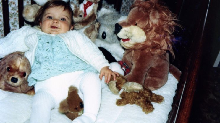Me as a baby surrounded by soft toy animals